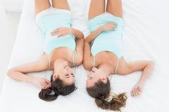 Twee vrouwelijke vrienden in wintertalingsmouwloze onderhemden die in bed liggen Royalty-vrije Stock Afbeeldingen