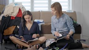 Twee vrouwelijke vrienden zitten samen op vloer van woonkamer en het bekijken tijdschriften, het wegknippen pagina's en het babbe stock footage
