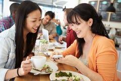 Twee Vrouwelijke Vriendenvrienden die voor Lunch in Koffiewinkel samenkomen royalty-vrije stock fotografie