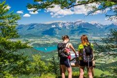 Twee vrouwelijke wandelaars die van schitterende mening over Meer genieten tapten en Alpen op de zomerdag af Stock Foto's