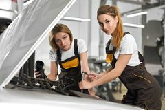 Twee vrouwelijke werktuigkundigen die auto in autoservice herstellen stock foto's