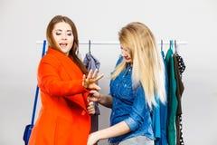 Twee vrouwen bij kleren het winkelen stock afbeeldingen