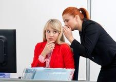 Twee vrouwen colegues roddel in bureau Stock Foto