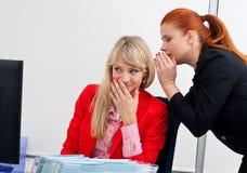 Twee vrouwen colegues roddel in bureau Royalty-vrije Stock Fotografie