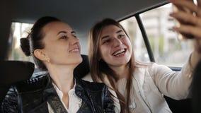 Twee vrouwen in de achterbank van auto's die in een een taxi, het spreken en gebruikssmartphone reizen stock footage