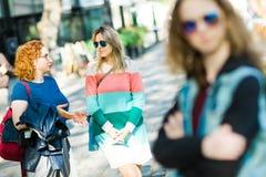 Twee vrouwen in de stad die samen - bored meisjeswachten lopen royalty-vrije stock foto's