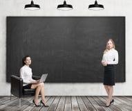 Twee vrouwen dichtbij bord Stock Foto's