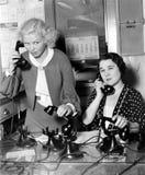 Twee vrouwen die aan een telefoonbank werken (Alle afgeschilderde personen leven niet langer en geen landgoed bestaat Leverancier Royalty-vrije Stock Afbeeldingen
