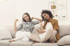 Twee vrouwen die aan muziek luisteren en oortelefoons delen royalty-vrije stock foto