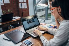 Twee vrouwen die aan nieuwe website werken ontwerpen het kiezen van beelden gebruikend laptop surfend Internet royalty-vrije stock foto's