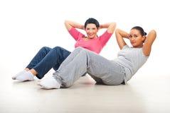 Twee vrouwen die abs doen stock afbeelding