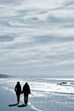 Twee vrouwen die bij het strand lopen stock foto