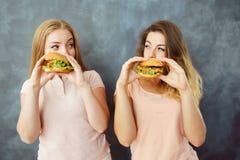 Twee vrouwen die burgers eten en bekijken elkaar stock afbeeldingen