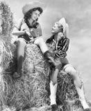 Twee vrouwen die in cowboyhoeden op een hooiberg zitten (Alle afgeschilderde personen leven niet langer en geen landgoed bestaat  stock afbeelding