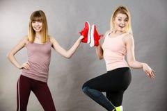 Twee vrouwen die de schoenen van sportkledingstrainers voorstellen Royalty-vrije Stock Afbeeldingen