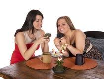 Twee vrouwen die de telefoons van de koffiecel zitten Stock Afbeeldingen