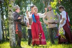 Twee vrouwen die in een cirkel van mensen dansen - ??n van hen spelen de harmonika en het zingen stock afbeeldingen