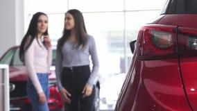 Twee vrouwen die een nieuwe auto bespreken bij de het handel drijventoonzaal stock footage