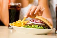 Twee vrouwen die hamburger eten en soda drinken stock afbeelding