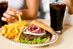 Twee vrouwen die hamburger eten en soda drinken royalty-vrije stock foto