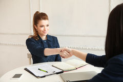 Twee vrouwen die handen schudden bij een bureau Royalty-vrije Stock Fotografie