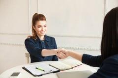 Twee vrouwen die handen schudden bij een bureau Stock Afbeeldingen