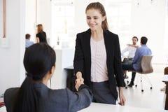Twee vrouwen die handen schudden op een vergadering in een open planbureau stock afbeeldingen