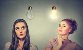 Twee vrouwen die het bekijken omhoog gloeilampen denken stock foto
