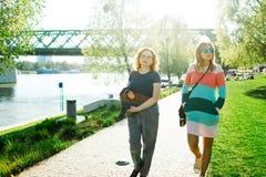 Twee vrouwen die langs de waterkant lopen stock foto