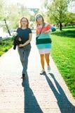Twee vrouwen die langs de waterkant lopen - schaduwen stock fotografie