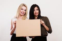 Twee vrouwen die lege raad houden stock foto
