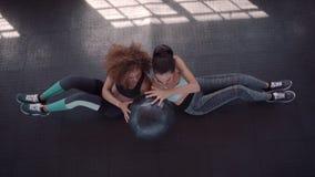 Twee vrouwen die met geneeskundebal uitoefenen in gymnastiek stock videobeelden