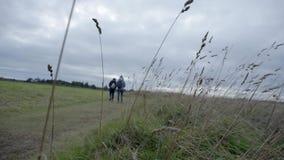 Twee vrouwen die met hun ruggen aan de camera, samen door het Culloden-Slagveld lopen stock videobeelden
