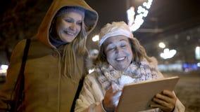 Twee vrouwen die met stootkussen openlucht in de koude lopen