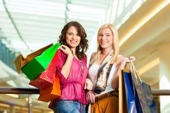 Twee vrouwen die met zakken in wandelgalerij winkelen stock foto's