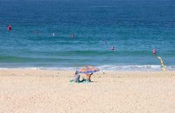Twee vrouwen die onder parasol op zandig strand zitten royalty-vrije stock foto