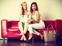 Twee vrouwen die op bank zitten die zak voorstellen Stock Foto's