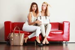 Twee vrouwen die op bank zitten die zak voorstellen stock foto