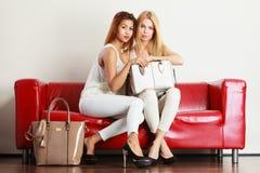 Twee vrouwen die op bank zitten die zak voorstellen stock fotografie