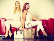 Twee vrouwen die op bank zitten die zakken voorstellen Stock Fotografie