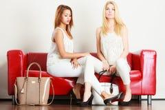 Twee vrouwen die op bank zitten die zakken voorstellen stock foto