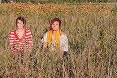 Twee Vrouwen die op een Gebied zitten Royalty-vrije Stock Foto's