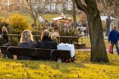 Twee vrouwen die op een parkzetel ontspannen royalty-vrije stock foto
