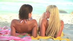Twee vrouwen die op handdoeken op het zand liggen stock video