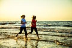 Twee vrouwen die op strand lopen royalty-vrije stock foto's