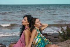 Twee vrouwen die op zand dichtbij het overzees zetten Royalty-vrije Stock Foto's