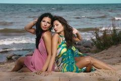 Twee vrouwen die op zand dichtbij het overzees zetten Stock Afbeeldingen