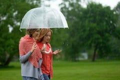 Twee vrouwen die park in regen en bespreking lopen Vriendschap en mensenmededeling stock fotografie