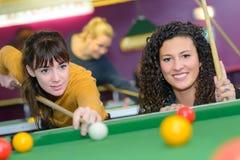 Twee vrouwen die pool spelen stock afbeeldingen
