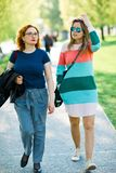 Twee vrouwen die samen - hebbend rusttijd lopen stock afbeelding